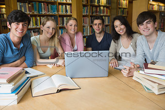 Six students learning in a library with a laptop