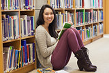 Student in a library leaning against a shelf