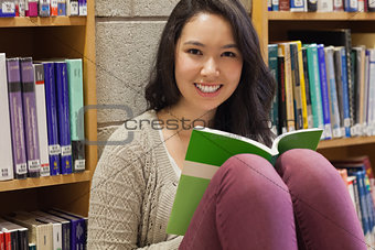 Student in a library sitting on the floor