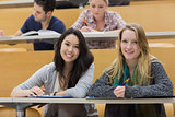 Girls smiling in lecture hall with tablet pc