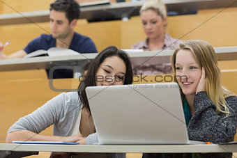 Students in a lecture hall with a laptop