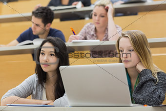 Students in a lecture hall using a laptop