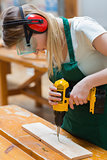 Student in a woodwork class using a drill