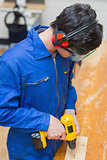 Student at a workbench using the drill
