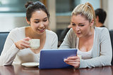 Two students in a coffee shop using a tablet pc