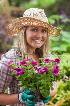 A woman is holding flowers in the garden