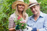 Blonde woman and man holding potted plant