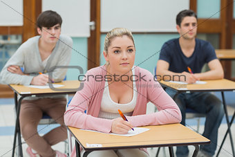 Three students in a classroom about to take notes