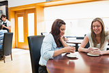 Two woman sitting in cafeteria and drinking coffee
