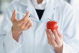 Woman injecting liquid in tomato