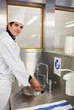 Cheerful chef washing hands