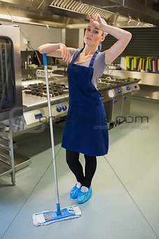 Tired woman cleaning the kitchen floor