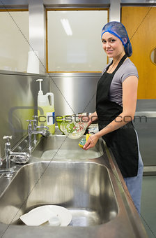 Smiling woman washing the dishes