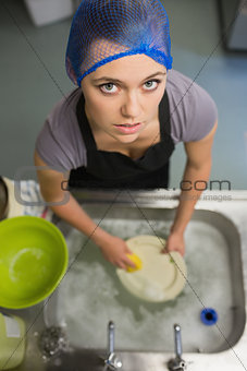 Woman looking up from doing the washing up