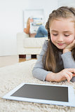 Girl using tablet with her mother reading the newspaper on the couch