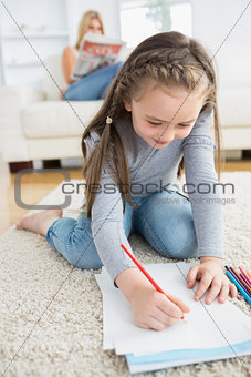 Little girl drawing sitting on floor with mother reading newspaper
