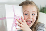 Surprised girl shaking a present
