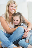 Mother and daughter hugging in living room