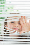 Happy child peeking through blinds