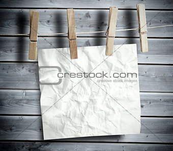 Crumpled paper hanging with pegs