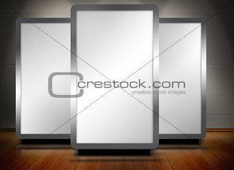 Three blank screens standing on wooden floor