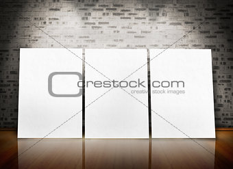 Three posters standing in line in a parquet floor like an art exhibition