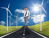 Businessman running on a road next to windmills
