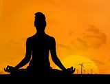 Silhouette of woman doing yoga in front of the sunset