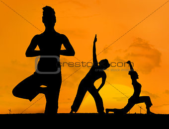 Silhouette of women practicing yoga