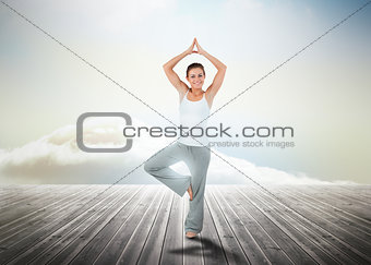 Woman practicing yoga over wooden boards