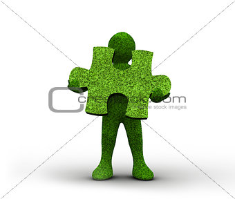 Green human representation holding a grass jigsaw puzzle