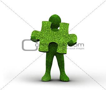 Green human representation holding a grass jigsaw puzzle
