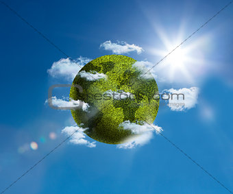 Green planet floating bright blue sky