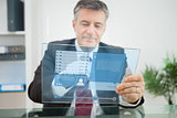 Businessman using futuristic touchscreen to view social network profile