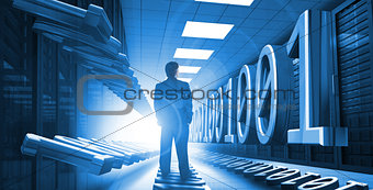Businessman standing in data center with binary code