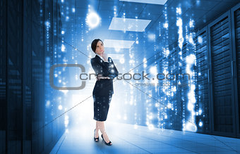 Businesswoman standing and looking thoughtful in data center