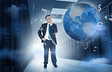 Businessman standing in data center with currency graphics and earth