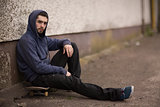 Skater taking a break outside the skate park and looking at camera