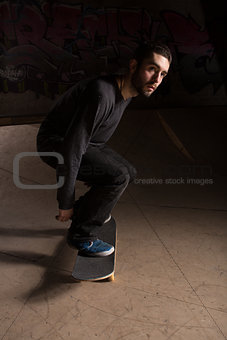 Skater bending his knees to prepare for a trick