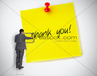 Businessman writing thank you on a giant post it