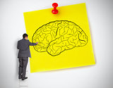 Businessman drawing a brain on a giant post it