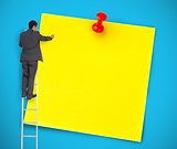 Businessman writing on a giant yellow post