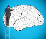 Businessman drawing a brain on a giant wall