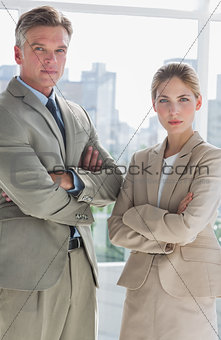 Business people standing with their arms crossed