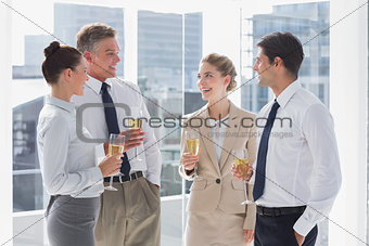 Group of cheerful business people clinking their flutes of champagne