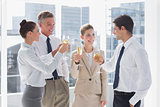 Smiling team of business people clinking their flutes of champagne