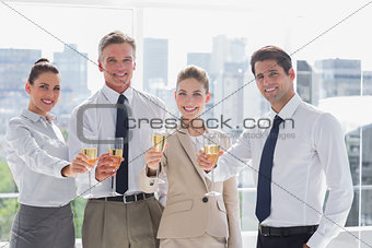 Smiling team of business people honoring a success with champagne