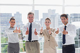 Smiling team of business people giving thumbs up