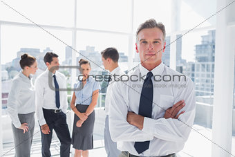 Serious boss with arms folded standing in a modern office