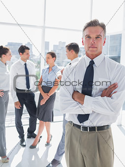 Boss standing with arms folded in a modern office